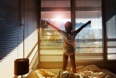 Junge, der auf seinem Bett steht und heraus das Fenster schaut Stockbilder