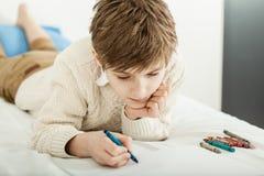 Junge, der auf seiner Bettzeichnung liegt Lizenzfreie Stockbilder
