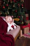 Junge, der auf Sofa nahe Weihnachtsbaum mit Geschenken schläft Lizenzfreies Stockfoto