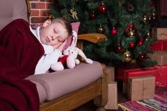 Junge, der auf Sofa nahe Weihnachtsbaum mit Geschenken schläft Stockfoto