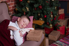 Junge, der auf Sofa nahe Weihnachtsbaum mit Geschenken schläft Lizenzfreie Stockfotos