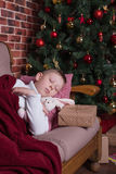 Junge, der auf Sofa nahe Weihnachtsbaum mit Geschenken schläft Stockbilder