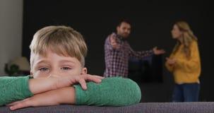 Junge, der auf Sofa während Eltern zu Hause argumentieren im Hintergrund 4k sich lehnt stock video footage