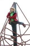 Junge, der auf Spielplatz klettert Stockbilder