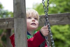 Junge, der auf Spielplatz klettert Lizenzfreie Stockbilder