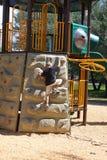 Junge, der auf Spielplatz steigt Lizenzfreie Stockbilder