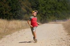 Junge, der auf staubige Straße läuft Stockfotografie