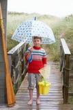 Junge, der auf Steg mit Regenschirm steht Lizenzfreie Stockbilder