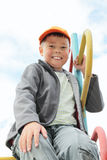 Junge, der auf steigendem Treppenhaus sitzt Lizenzfreie Stockfotografie