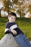 Junge, der auf Stein sich lehnt Lizenzfreie Stockfotos