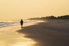 Junge, der auf Strand am Sonnenuntergang geht Lizenzfreie Stockbilder