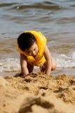 Junge, der auf Strand spielt lizenzfreie stockbilder