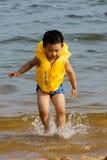 Junge, der auf Strand spielt stockfoto