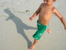 Junge, der auf Strand spielt Stockfotos