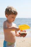 Junge, der auf Strand spielt Stockbild