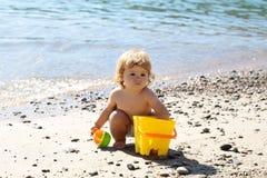 Junge, der auf Strand spielt Lizenzfreie Stockfotos