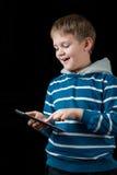 Junge, der auf Tablette spielt Stockfotografie