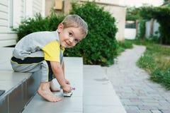 Junge, der auf Treppe auf der Rückseite seines Hauslächelns sitzt Stockfoto