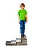 Junge, der auf Treppe von Büchern steht Stockbild