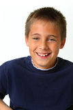 Junge, der auf weißem Hintergrund lacht Lizenzfreie Stockfotografie