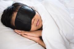 Junge, der auf weißem Kissen und Blättern des Betts mit Schlafmaske schläft Lizenzfreies Stockfoto