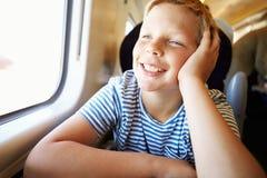Junge, der auf Zug-Reise sich entspannt lizenzfreies stockbild