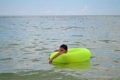 Junge, der in aufblasbaren Ring schwimmt Stockbild