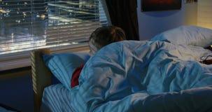 Junge, der aus Fenster heraus beim Lügen im Bett schaut stock footage