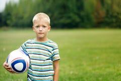 Junge, der Ball steht und hält Lizenzfreies Stockbild