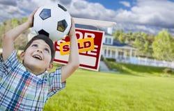 Junge, der Ball vor Haus und Verkaufszeichen hält Stockbild