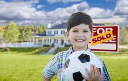 Junge, der Ball vor Haus und Verkaufszeichen hält Stockfotografie