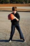 Junge, der Basketball auf einem Spielplatz spielt Stockfotos
