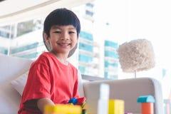 Junge, der Baukl?tze auf einem Wohnzimmer f?r p?dagogisches Spielzeug stapelt stockfotografie
