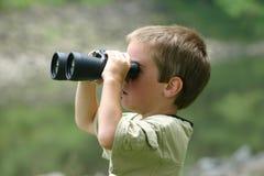 Junge, der Binokel verwendet Stockbilder