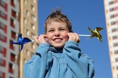 Junge in der blauen Jacke mit Pinwheels in den Händen Stockfotografie