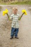 Junge, der Blumen hält Stockfotografie