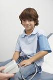 Junge, der Blutdruck nehmen lässt Stockbilder
