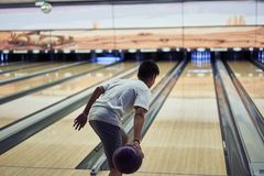 Junge, der Bowlingspiel spielt lizenzfreie stockfotografie
