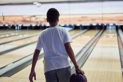 Junge, der Bowlingspiel spielt stockfotografie
