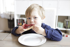 Junge, der Brot und Marmelade isst Lizenzfreie Stockbilder