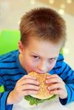 Junge, der Burger isst Stockbild