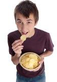 Junge, der Chip-Imbiß isst und oben schaut Stockfotografie