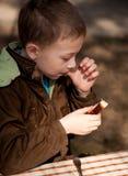 Junge, der das Brot und die Butter auf der geöffneten Luft enjoing ist stockbild