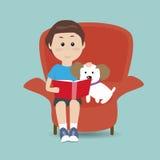 Junge, der das Buch auf dem Sofa mit seinem Hund liest Stockbild