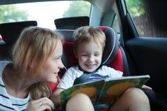 Junge, der das Buch sitzt in einem Auto mit Mutter hält Stockbild