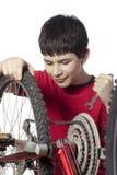 Junge, der das Fahrrad repariert Stockfotografie