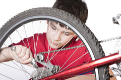 Junge, der das Fahrrad repariert Lizenzfreie Stockfotos