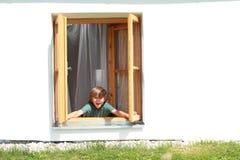 Junge, der das Fenster öffnet Stockfotografie