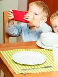 Junge, der das Frühstück essend spielt mit Handy geifert Stockfoto