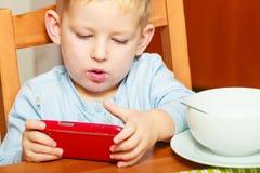 Junge, der das Frühstück essend spielt mit Handy geifert Lizenzfreie Stockfotografie